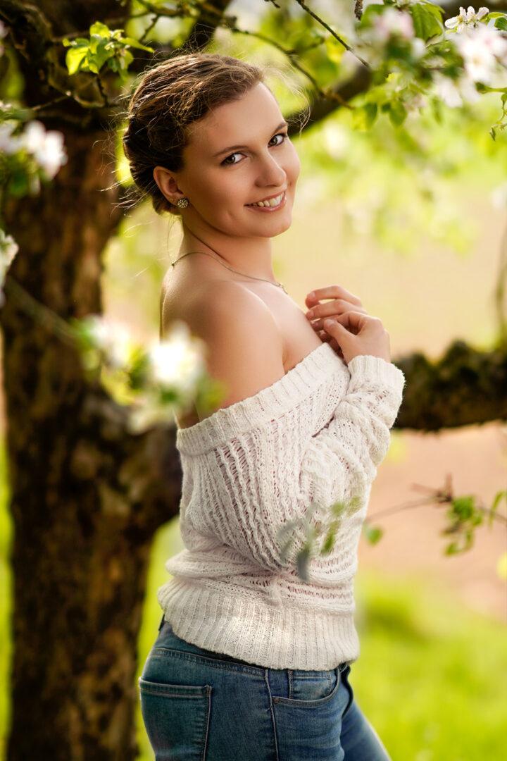 Frau Portraitshooting mit weißen Blüten und Top im Frühling